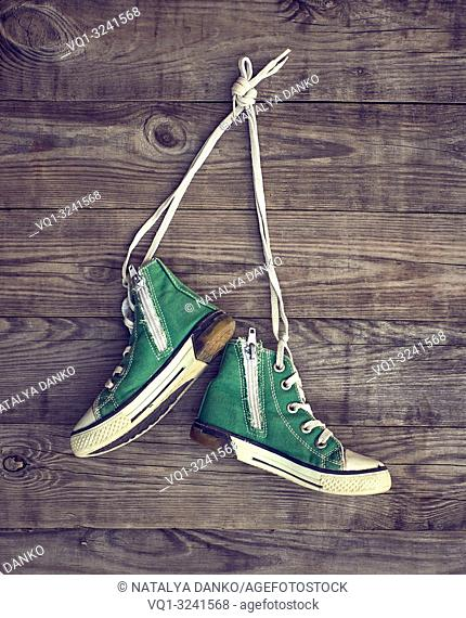 pair of old green textile sneakers hang from laces on a gray wooden wall, copy space