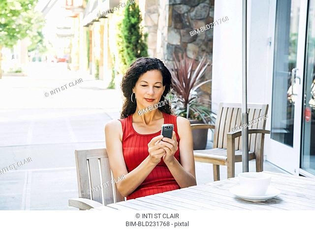 Mixed Race woman texting on cell phone at cafe