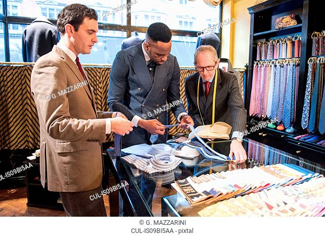 Tailors and customer choosing shirt and tie in tailors shop