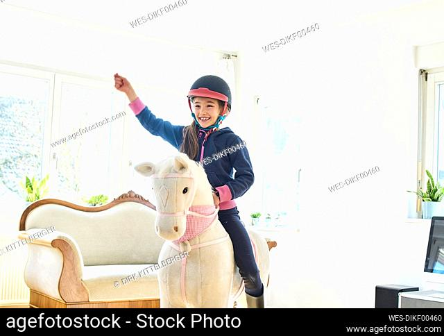 Girl riding on play horse at home