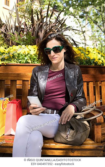 brown hair woman with white jeans, red shirt, leather blazer jacket and sunglasses sitting in wooden bench, at street, with shopping bags and puse