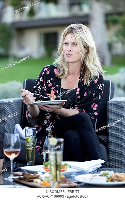 An attractive woman relaxes at an outdoor patio with food and drink while visiting the Kingfisher resort in Courtenay. Vancouver Island, British Columbia
