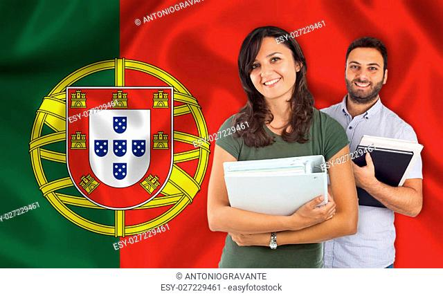 Couple of young students with books over Portuguese flag
