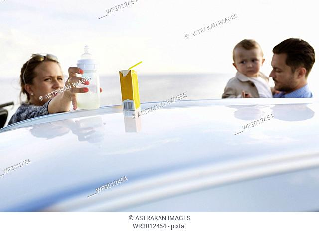 Parents with son (18-23 months) behind car