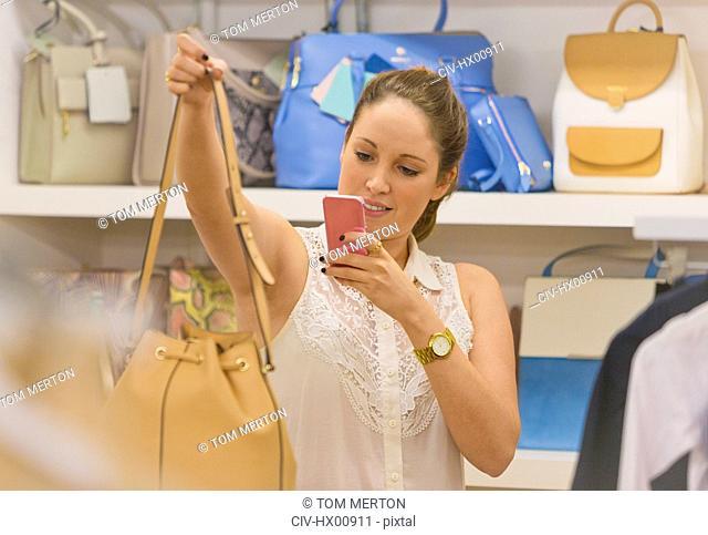 Shopper photographing handbag with camera phone