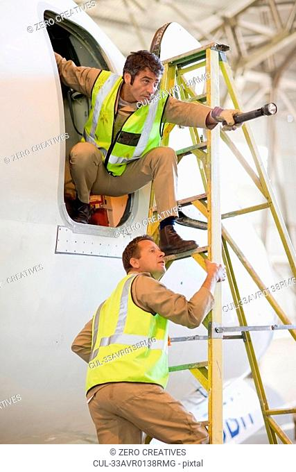 Aircraft workers talking on ladder