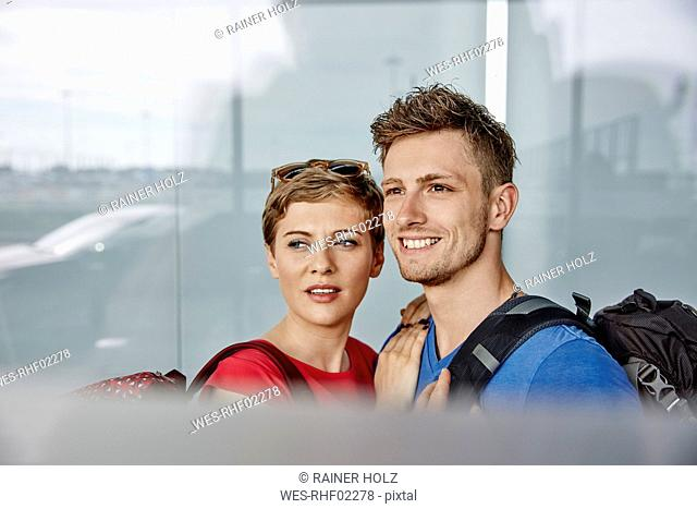 Portrait of smiling couple at the airport looking out of window