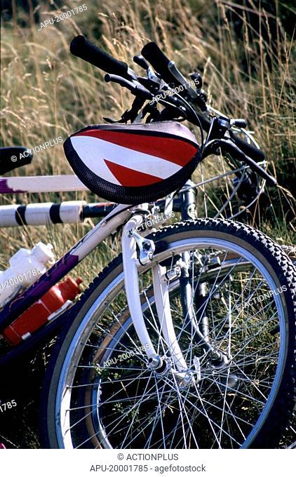 Two mountain bikes stacked on grass