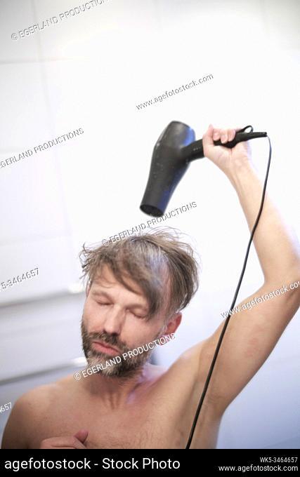 Man using hair dryer