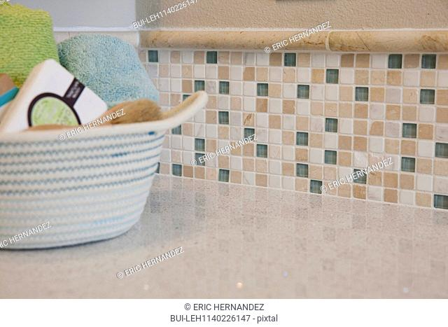Close-up of rolled towels in basket on countertop in the bathroom at home