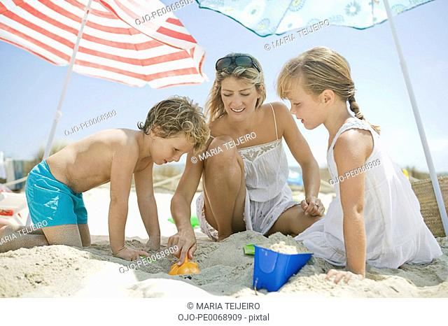 Family playing in sand on beach