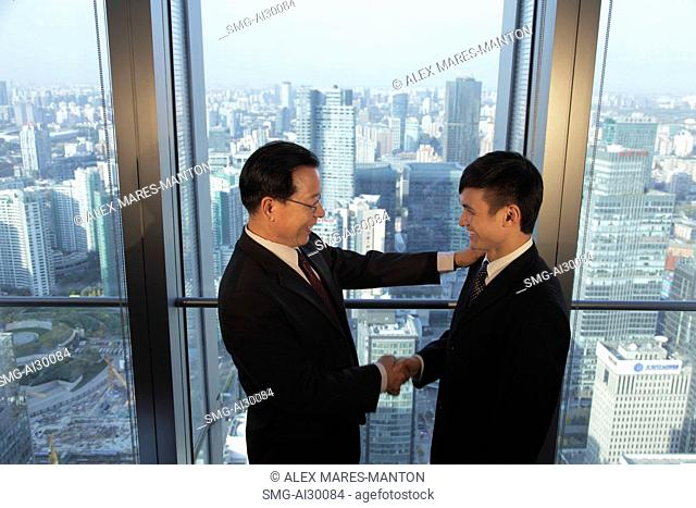Two men shaking hands in front of window with a view of the city of Beijing