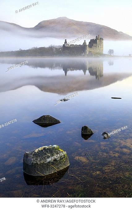 Kilchurn Castle and it's mountainous snow capped backdrop reflected on the still surface of Loch Awe on a misty moring