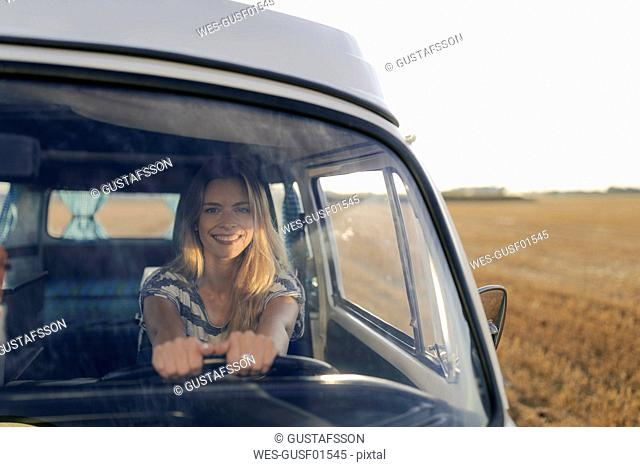 Happy young woman driving camper van in rural landscape