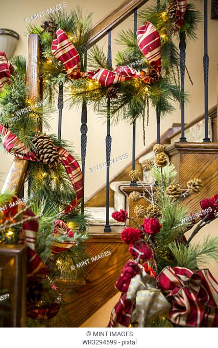 Banister decorated with boughs and string lights for Christmas