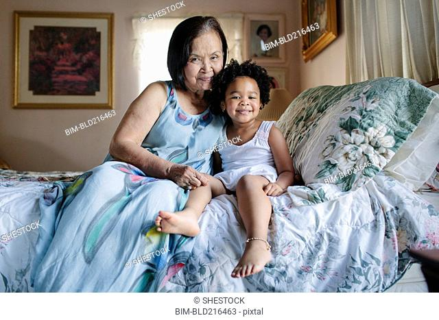 Grandmother and granddaughter hugging on bed