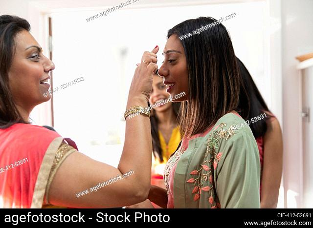 Indian woman placing bind on forehead of sister
