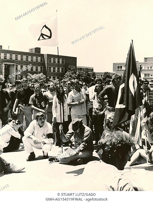 Students wearing hippie attire gather in a large group on a quad, with one student wearing a cowboy hat, looking downward