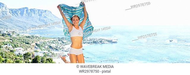 Woman in underwear with blanket celebrating against blurry coastline 3d