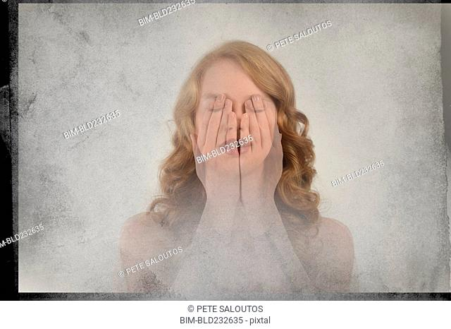 Double exposure of Caucasian woman covering face with hands