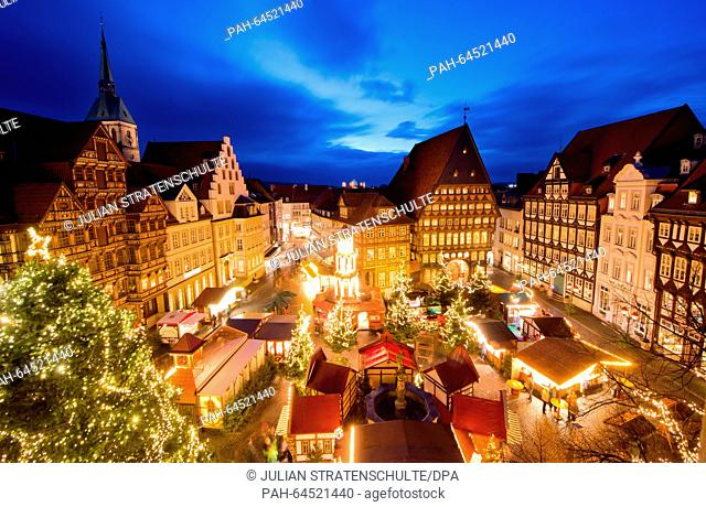 Festively decorated stalls, Christmas trees, and lights illuminate the Christmas market at the historic marketplace during blue hour in Hildesheim, Germany