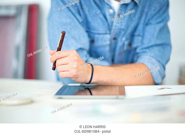 Cropped shot of male designer using digital tablet in printing press studio