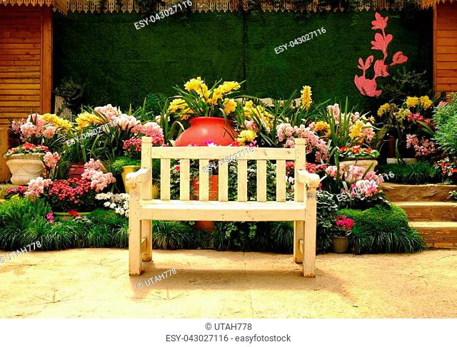 Empty wooden bench during a stroll in the park and flowers