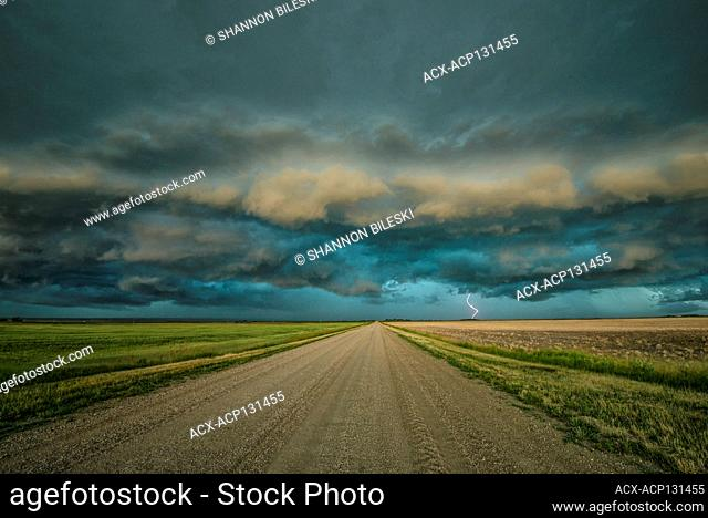 Storm with shelf cloud and lightning over rural gravel road in Saskatechewan Canada