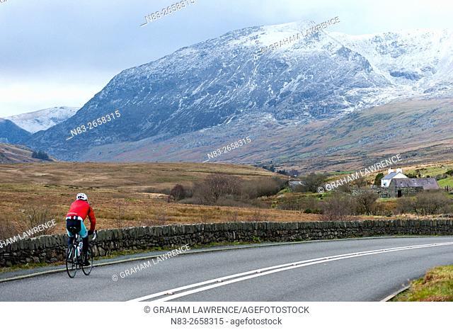 A cyclist on the A5 road near Capel Curig in Snowdonia National Park, Gwynedd, Wales, UK
