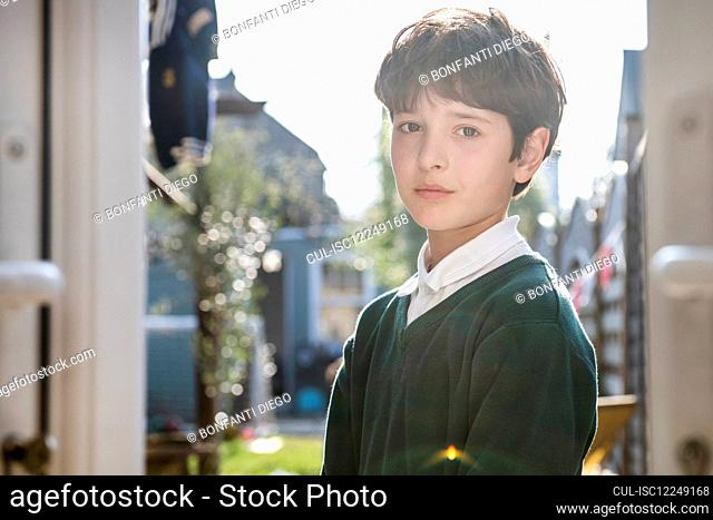 Portrait of boy with brown hair wearing green jumper, standing outdoors, looking at camera