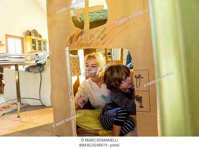 Caucasian boy and girl playing in cardboard house
