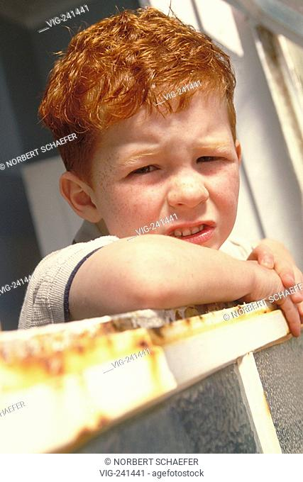 portrait, close-up, redheaded sad boy with freckles, 6 years, wearing white shirt and blue trousers with flap looking out of a window with a rusty frame  -...