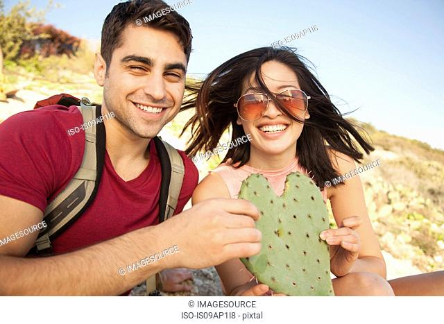 Young couple holding heart shaped cactus leaf