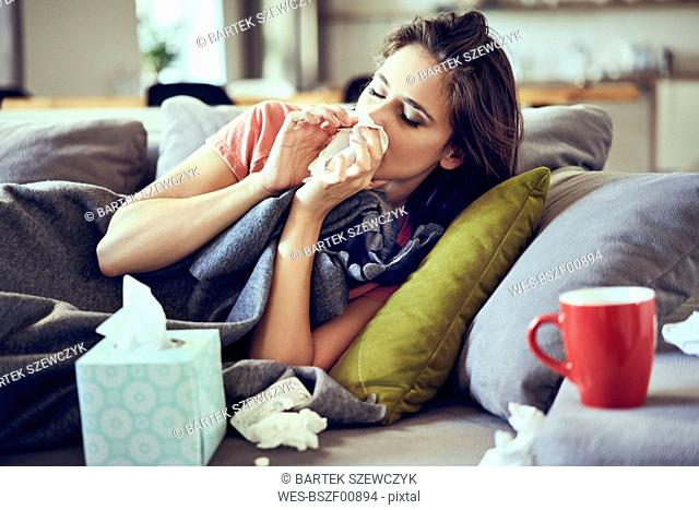 Portrait of young woman lying sick with the flu on sofa and blowing nose