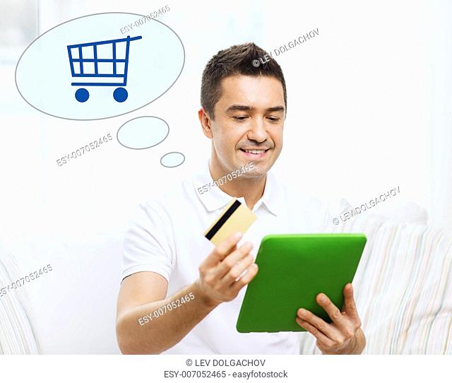 technology, online, sale and people concept - happy man with tablet pc computer, credit card and shopping trolley icon at home