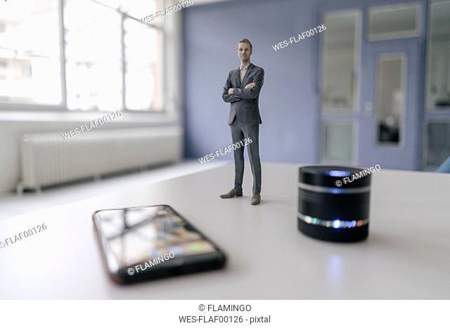 Miniature businessman figurine standing next to smart home loudspeaker and smartphone