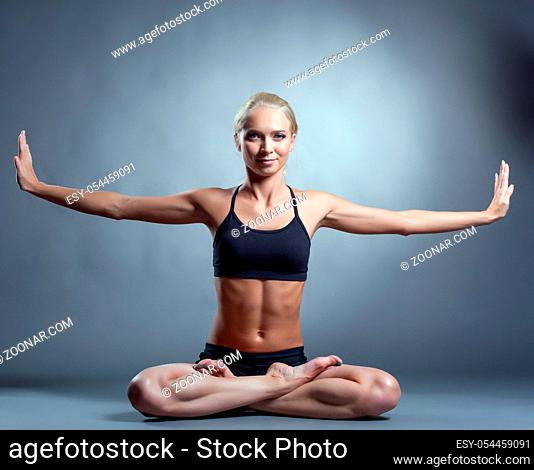 Image of beautiful slim woman doing yoga in studio
