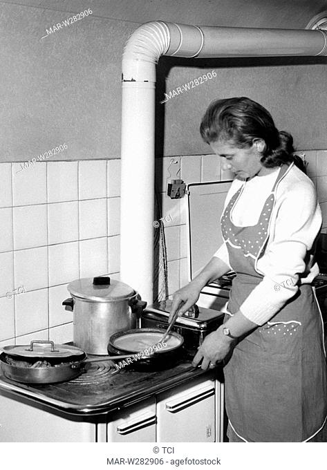 housewife preparing bagna cauda, a warm dip typical of piedmont, italy 1965