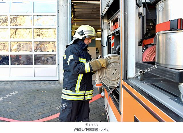Firefighter taking firehose from fire engine