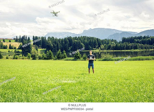 Germany, Bavaria, Pfronten, young man flying his drone at lakeside