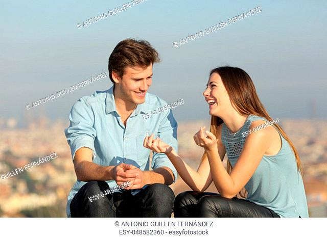 Happy couple dating talking together in a sunny day in a city outskirts