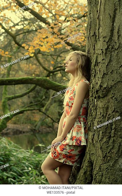 Beautiful young woman leaning against a tree