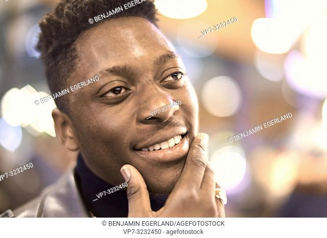 headshot of young man in city lights with positive mindset, African descent, looking aside, thinking about ideas, in Munich, Germany