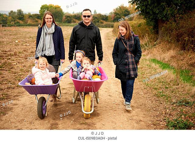 Portrait of parents pushing three girls in wheelbarrows along pumpkin field