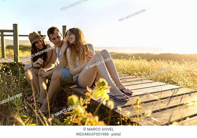 Friends sitting on boardwalk at the beach, drinking beer at sunset