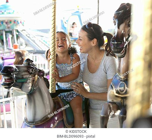 Hispanic mother and daughter riding carousel