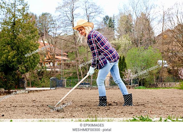Young woman raking