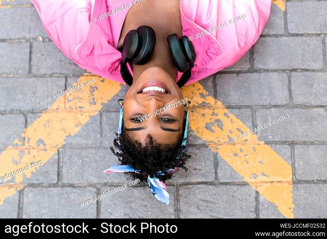 Smiling young woman lying on road outdoors