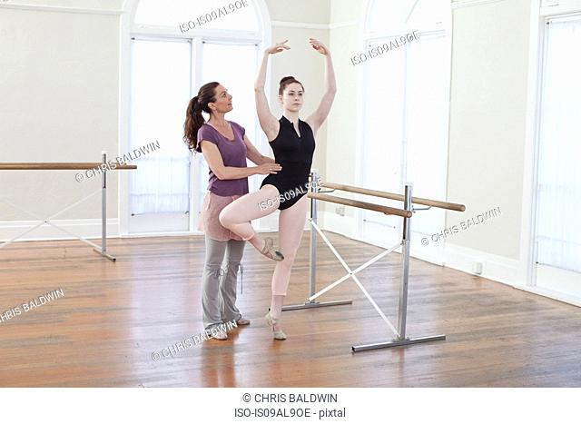 Teacher teaching ballet position to teenage ballerina at ballet school