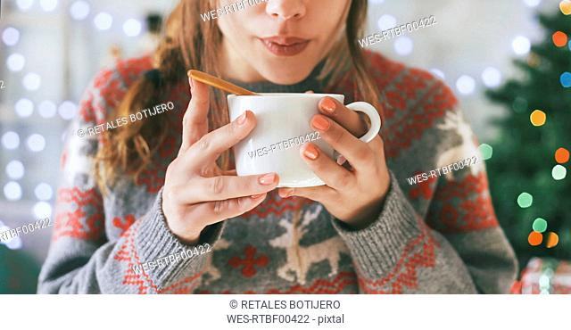 Woman with cup of coffee at Christmas time, close-up